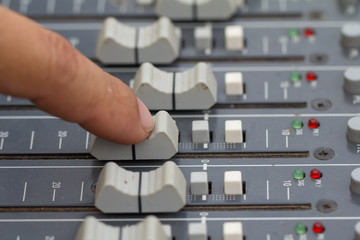 An expert adjusting audio mixing console.select focus