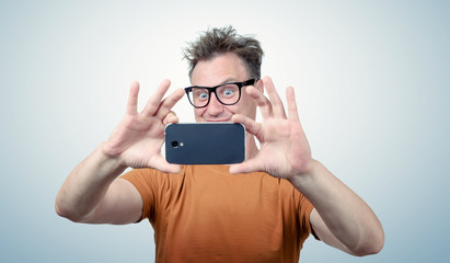 Happy man in glasses photographed by smartphone