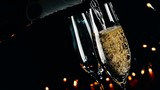 champagne into flutes with bubbles on black light background poster