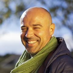 Hombre calvo con fular verde sonriendo