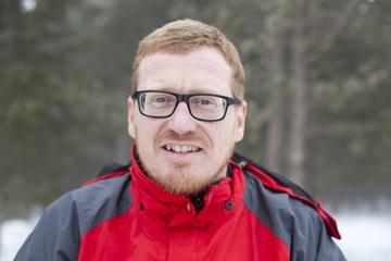 Hombre pelirrojo con gafas negras en la nieve