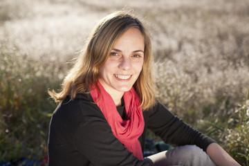 Mujer rubia con fular rojo en el campo