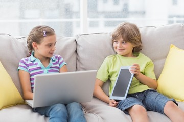 Happy siblings using technologies on sofa