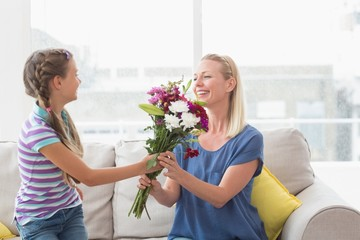 Girl giving bouquet to mother at home