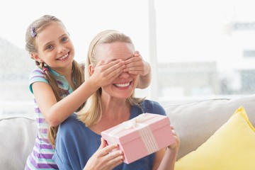 Mother holding gift with daughter covering her eyes