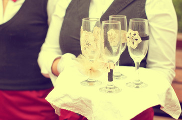 waiter holding a plate with 4 empty champagne glasses