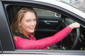Young woman driving and smiling