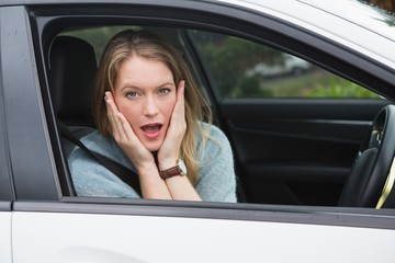 Shocked woman sitting in drivers seat