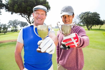 Golfing friends showing their cups