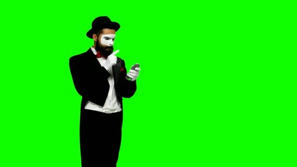 Man mime shows something using remote control on green screen