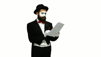 Unhappy man mime reads about something on paper, white