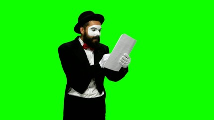 Happy man mime reads about something on paper, green screen