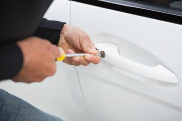Thief breaking into car with screwdriver