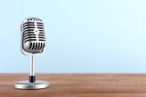 Fototapety Retro microphone on wooden table on light background
