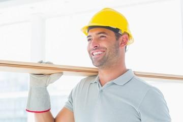 Smiling handyman carrying wood