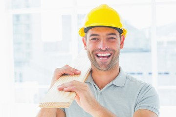 Cheerful male carpenter carrying planks