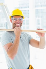 Happy carpenter carrying wood in building