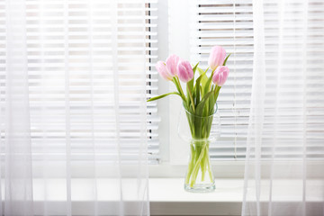 Beautiful pink tulips in glass vase on windowsill background