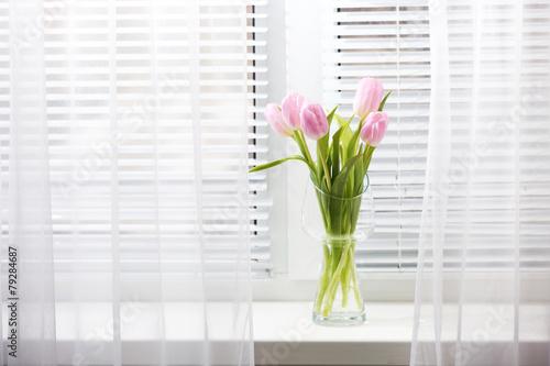 Foto op Aluminium Tulp Beautiful pink tulips in glass vase on windowsill background