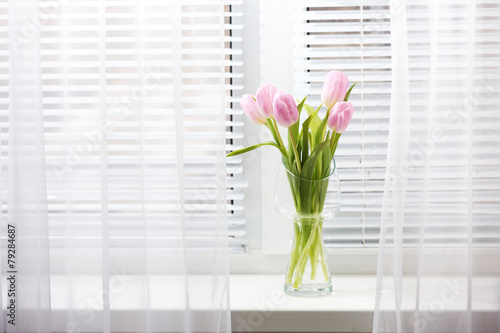 Foto op Canvas Tulp Beautiful pink tulips in glass vase on windowsill background