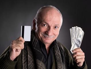Lucky elderly man holding dollar bills and credit card