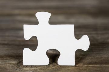 Ein Puzzleteil in weiß auf Holz Hintergrund