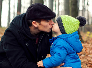 young dad kissing his son on autumn outdoor