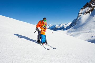Dad teach little son to ski in mountains