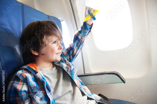 Little smiling boy with toy plane by the window - 79287007