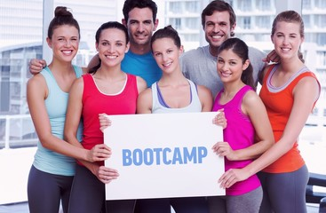Bootcamp against fit smiling people holding blank board