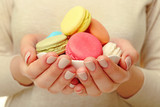 Cup of tasty colorful macaroons in female hands, closeup view