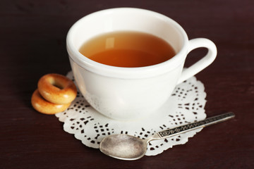 Cup of tea with bagels on color wooden table background