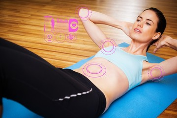 Composite image of fit brunette doing sit ups in fitness studio
