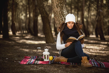 Young Girl Concentrated While Reading a Book in the Forest