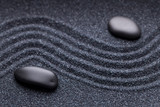 Zen garden with a wave lines in the sand with irregular black st
