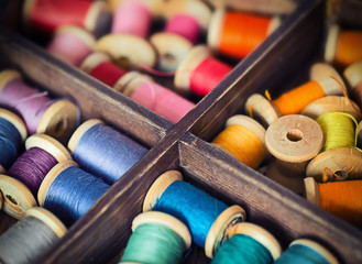 different color spools  threads in a grunge wooden box