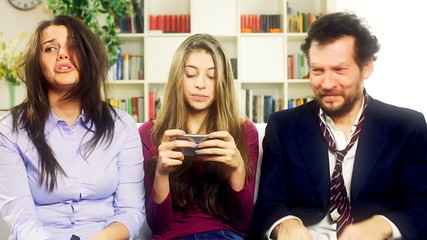 Father and mother trying to talk to daughter funny.