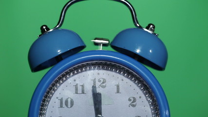 Ringing classical alarm clock  green background, twelve o'clock