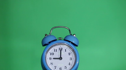 Ringing classical alarm clock green background, nine o'clock