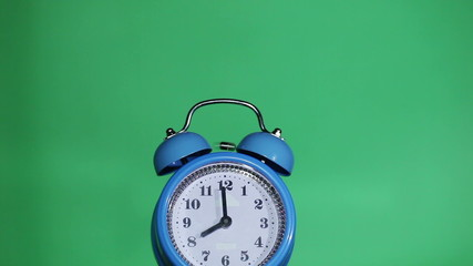 Ringing classical alarm clock  green background, eight o'clock