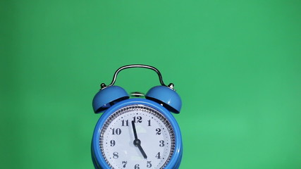 Ringing classical alarm clock ,  green background, five  o'clock