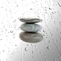 Three pebble stones on water drops background