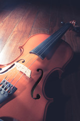 Wooden violin on wood surface.