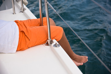 Young boy sitting on a yacht side