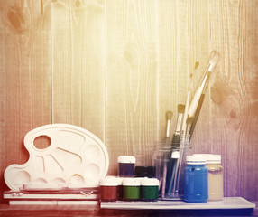Paintbrushes, watercolor, and paper are on wooden shelf