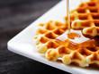 Leinwandbild Motiv Honey pouring on a fresh waffles