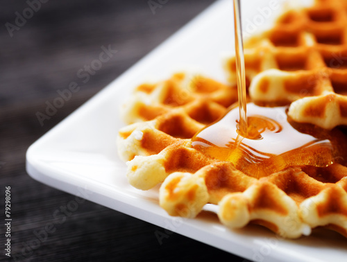 Honey pouring on a fresh waffles - 79298096