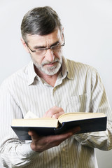 Middle aged bearded man reading a book