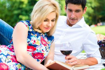 Paar trinkt Wein und liest Buch auf Wiese