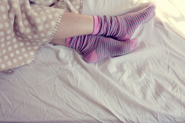 girl with pink striped socks, sleeping in bed